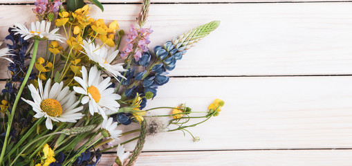 Wild flowers on old grunge wooden background (chamomile lupine dandelions thyme mint bells rape) Fotobehang