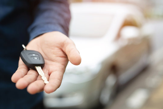 Car key, businessman handing over gives the car key to the other man on car background.