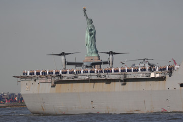 The USS New York Naval San Antonio-class amphibious transport dock ship makes its way past the Statue of Liberty in New York Harbor marking the beginning of Fleet Week  in New York