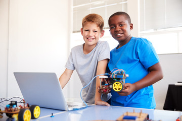 Portrait Of Two Male Students Building And Programing Robot Vehicle In School Computer Coding Class