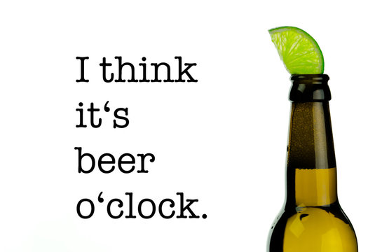 """An isolated brown beer bottle with a refreshing slice of lime and the quote """"I think it's beer o'clock"""" on a bright white background."""