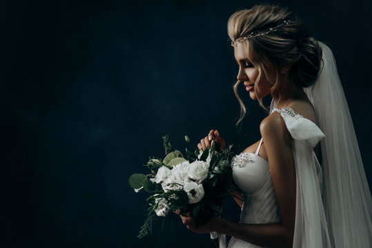 portrait of a luxurious bride on a dark background. Model with a beautiful make-up and hairstyle