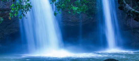 Fantastic tropical waterfall under the moonlight, gently water falling on the cliff, as a watercolor painting. Khao Yai, Thailand.