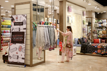A woman takes a photo of textiles while shopping at The Centaurus mall, ahead of Muslim holiday of Eid al-Fitr, which marks the end of the holy fasting month of Ramadan in Islamabad