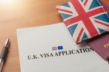 Visa application for uk on desktop with passport and union jack wallet Fotomurales