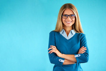 Happy business woman with crossed arms on blue background