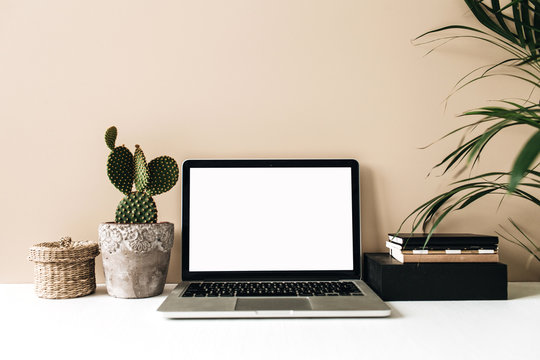 Minimalist home office desk workspace with laptop, cactus and palm on beige background. Front view copy space blank mock up. Blog, website, social media hero header template.