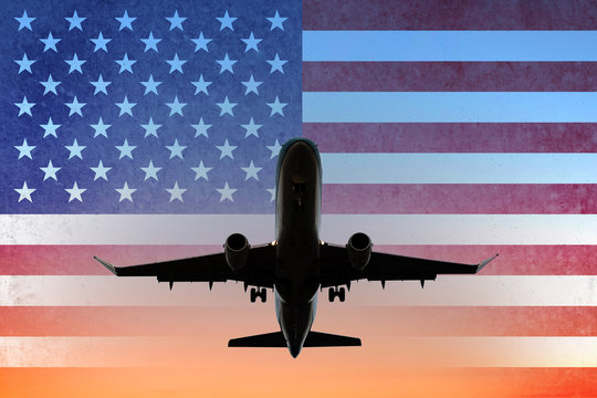 airplane on sunset sky with American flag - USA travel concept -