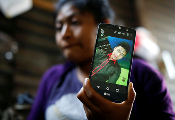 Rosa Elvira Hernandez shows a cell phone with the image of her brother Carlos Hernandez Vasquez, 16, at her home in the village of San Jose el Rodeo