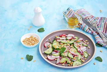 Light salad of crispy radish, cucumber and mint leaves with citrus dressing on a brown plate. Sprinkled with pine nuts.