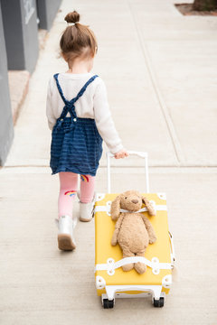 Girl pulling suitcase with teddy bear strapped to it