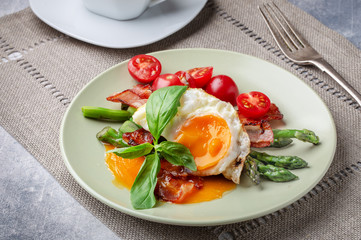 Fried egg with crispy bacon and asparagus on plate for breakfast