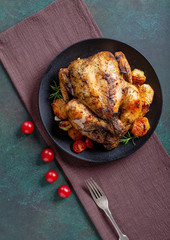 Grilled chicken on black plate, top view