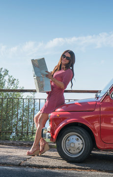 Woman holding map leaning on pink car