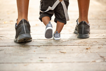 black father helping son walk