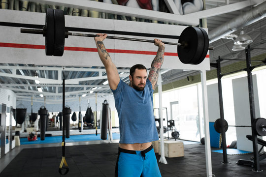 Mid adult man weight lifting in gym