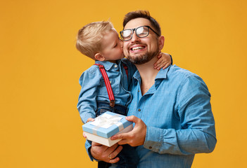 happy father's day! cute dad and son hugging on yellow background Wall mural