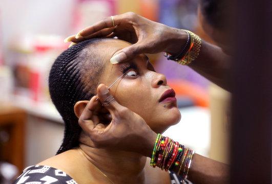 A woman gets fake eyelashes in a beauty salon in Abidjan