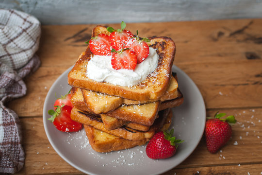 Close-up of french toast with fresh strawberries, coconut shreds and honey, on wooden background