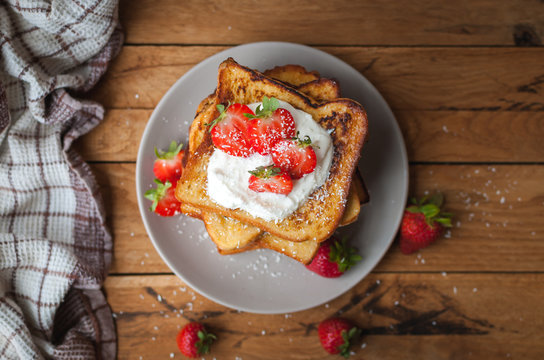 Close-up of french toast with fresh strawberries, coconut shreds and honey, on wooden background, top view