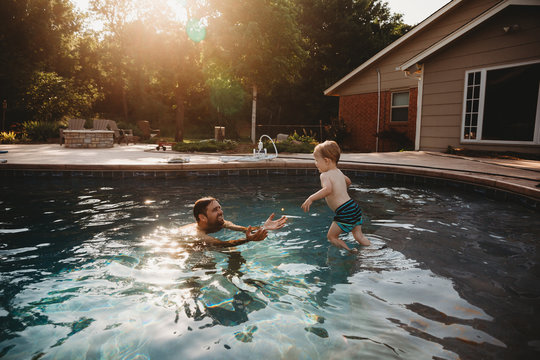Son jumping into fathers arms in pool