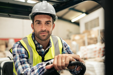 Smiling warehouse worker sitting in a forklift