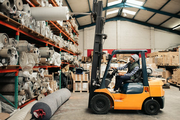 Forklift driver carefully moving stock around a large warehouse