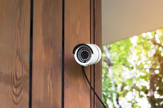 outdoor surveillance camera. white security camera on the wall of a wooden house on a green landscape background