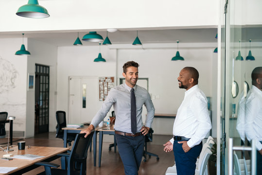 Two laughing businessmen talking together in an office