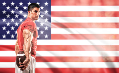 Muscualr Young Athlete Standing In Font of American Flag Holding American Football Ball in his hands