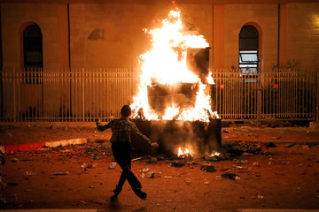 An Ultra-Orthodox Jewish boy dances around a bonfire as he celebrates the Jewish holiday of Lag Ba'Omer in the city of Ashdod