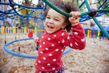 healthy african american little girl having a fun time. Crazy small kid bouncing back and forward in the playground outdoors