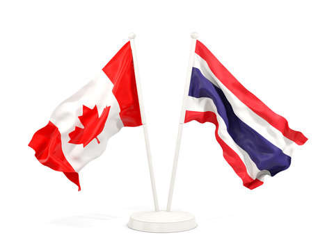 Two waving flags of Canada and thailand isolated on white