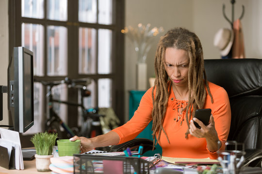 Busy Woman with Drealocks Reacting to Her Phone