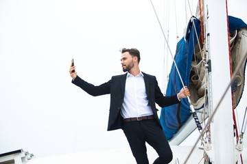 Luxury business man  taking selfie from phone on a sailing boat. Concept business travel