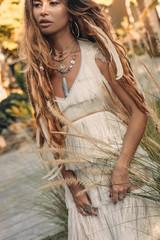 beautiful young stylish boho woman at sunset