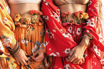 close up of two beautiful stylish boho model in colorful costumes with flowers