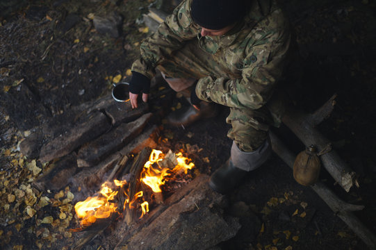 Man in camouflage drinking tea and warms himself by the fire in bad weather. Extreme travel. Survival in the wild.