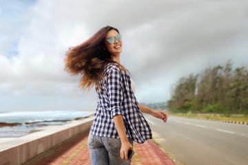 Woman looking back while walking on road beside sea