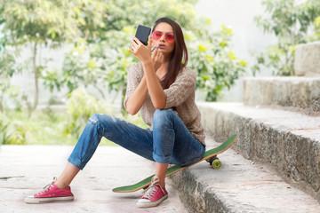 Woman sitting on a skateboard on steps applying lipstick