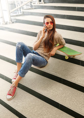 Woman sitting on steps with skateboard talking on mobile phone