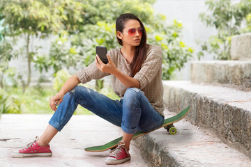 Woman sitting on skateboard on steps holding a small mirror