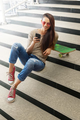 Woman sitting on steps with skateboard looking at mobile phone