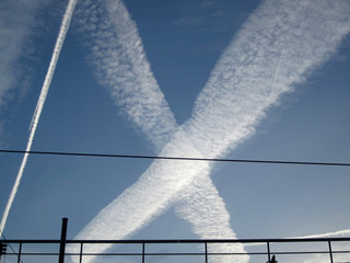 contrails forming a white cross against the blue sky