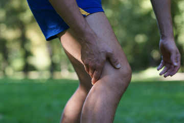 Muscle injury -  man with sprain thigh muscles after jogging in park. Athlete in sports shorts clutching his thigh muscles.