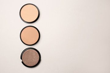 Different facial powder on light background