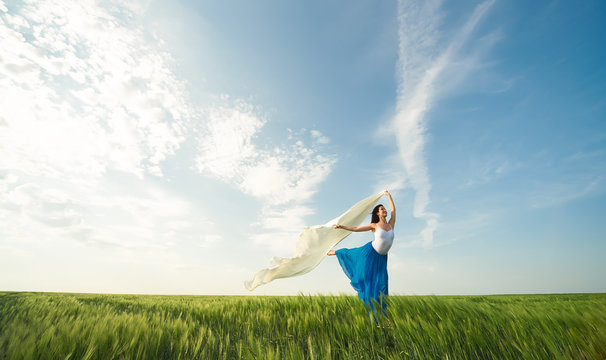 Flying dancer in the air. Happy woman ballerina in blue skirt making a big jump on Green field with white fabric. Summer or Spring concept