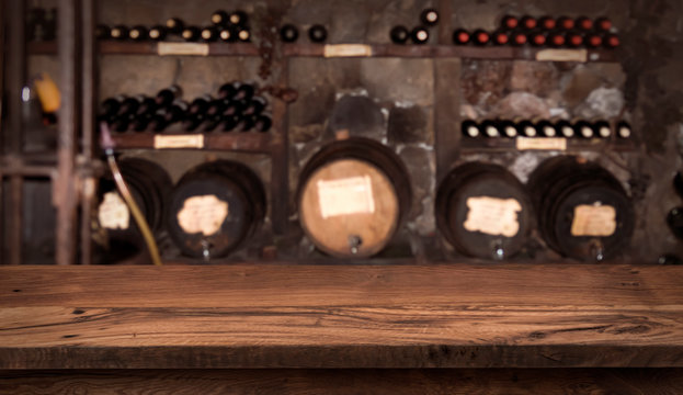 Wooden table on blurry background of wine barrels and bottles