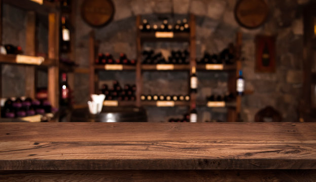 Defocused dark wine cellar background with wooden table in front