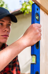 Young handsome man using spirit level in his work